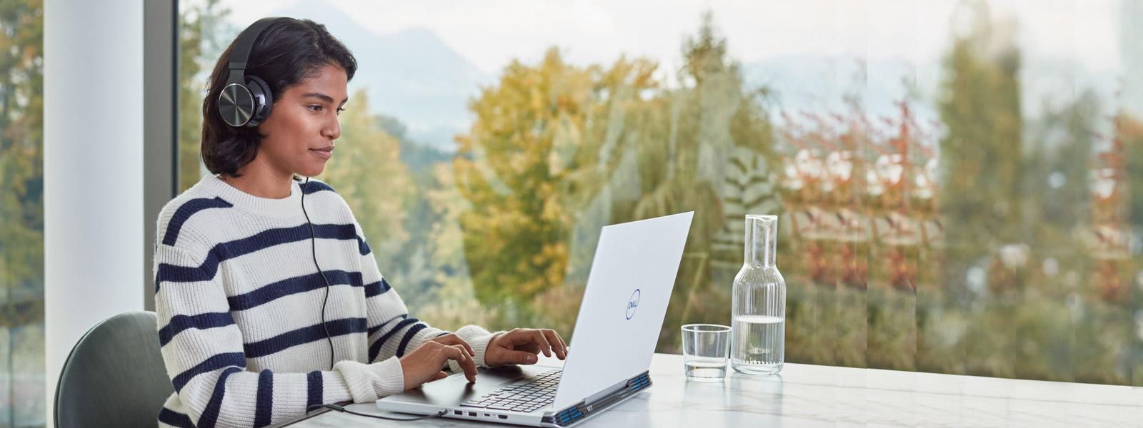 Un étudiant assis à une table travaillant sur un ordinateur portable et portant des écouteurs