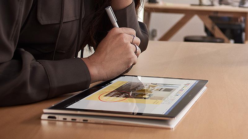 Un étudiant utilisant un stylet numérique sur son ordinateur Windows 10 2-en-1 pour créer une présentation PowerPoint
