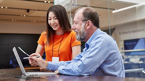 Employé de Microsoft qui paramètre les services infonuagiques sur un appareil Surface pour un client masculin.