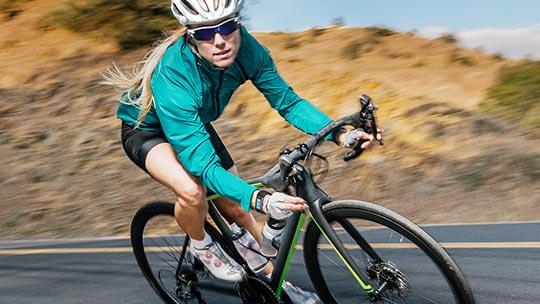 Femme en vélo sur une route montagneuse