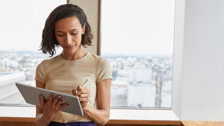 Une femme écrit avec un stylet pour Surface sur sa tablette Surface.