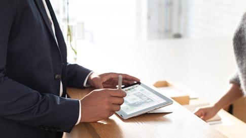 Une personne écrit avec un stylet Surface sur une Surface Go.
