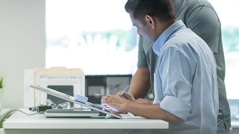 Un homme utilise un Surface Studio en mode de table à dessin.