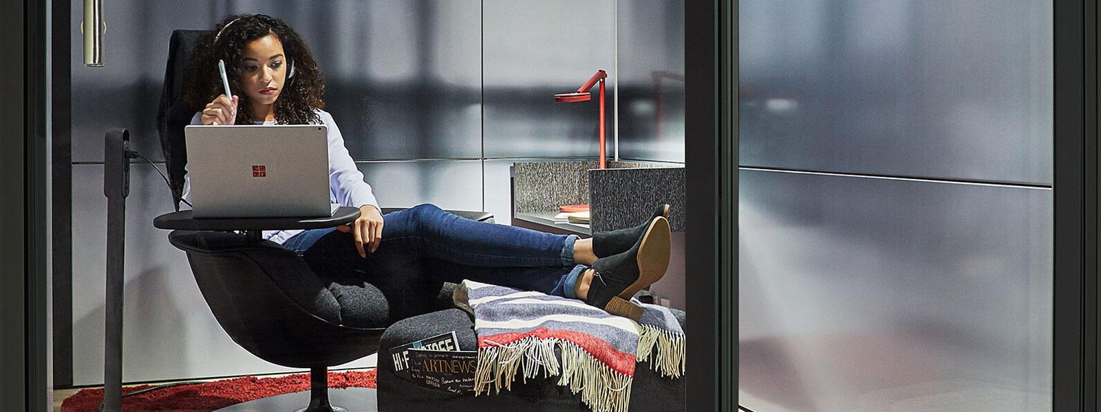 Femme assise dans un espace Steelcase, tenant un stylet Surface et regardant un Surface Book.