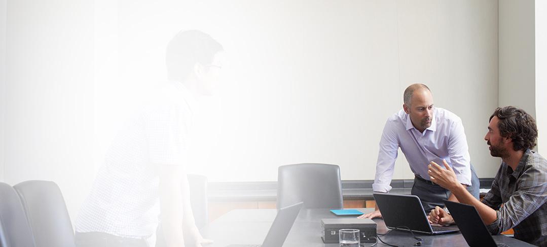 Trois hommes utilisant Office365 EntrepriseE4 sur des ordinateurs portables au cours d'une réunion dans une salle de conférence.