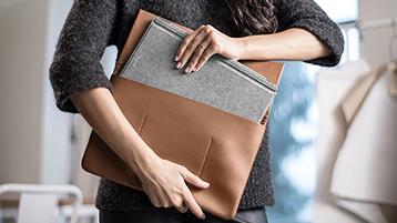 Femme plaçant une Surface Pro avec clavier Type Cover Signature dans un étui d'ordinateur portatif.
