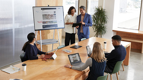 Une femme dessine sur un Surface Hub dans une réunion de bureau avec plusieurs personnes autour d'une table.