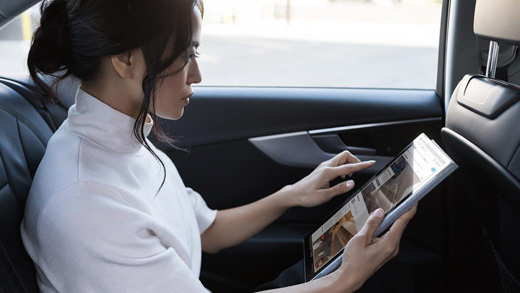 Femme utilisant Surface Pro avec LTE Advanced sur le siège arrière d'une voiture