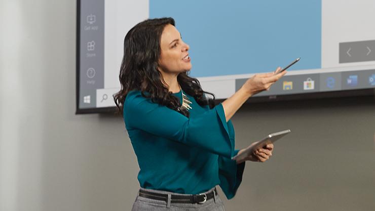 Technicienne qui pointe une présentation à l'écran.