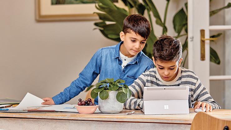 Deux élèves de sexe masculin regardant une tablette Surface.