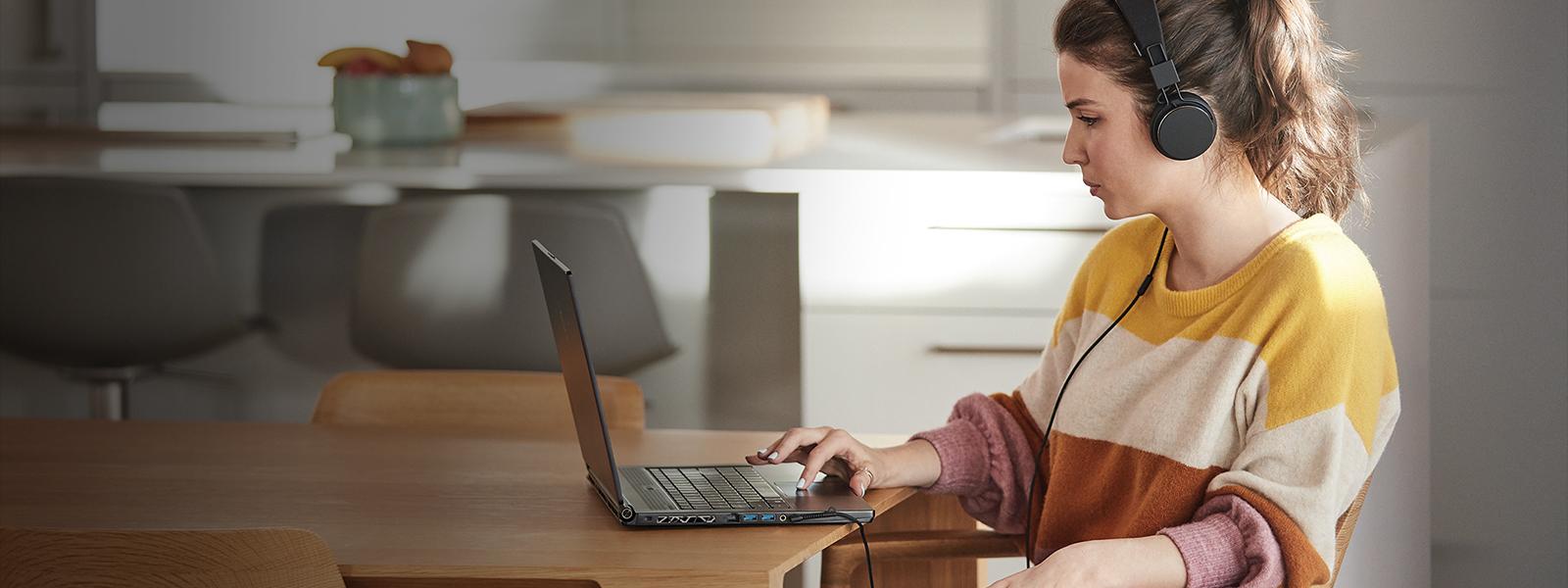 Femme travaillant sur un ordinateur avec des écouteurs.
