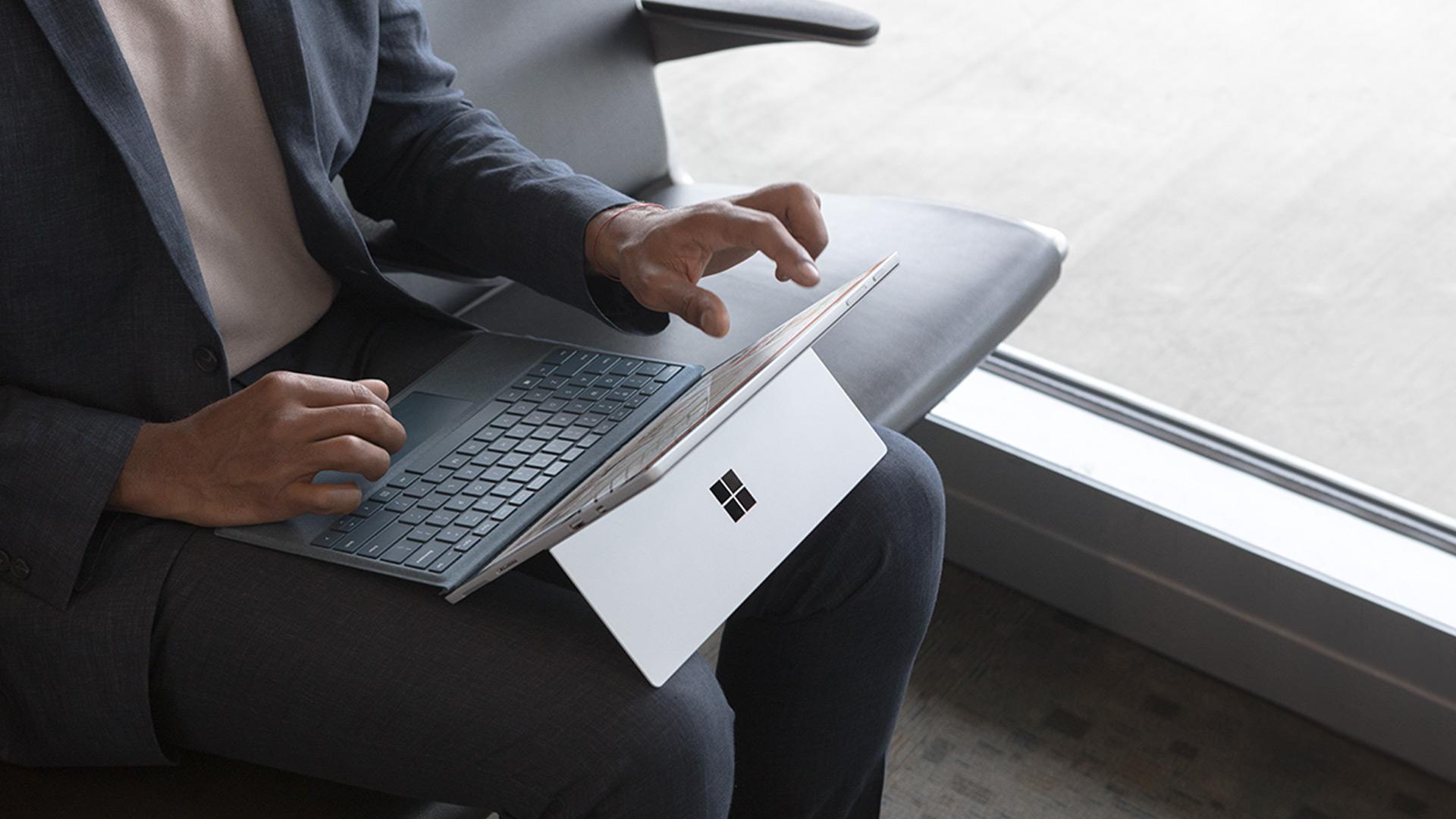 Une personne travaille dans une salle d'attente d'aéroport avec une SurfacePro sur les genoux