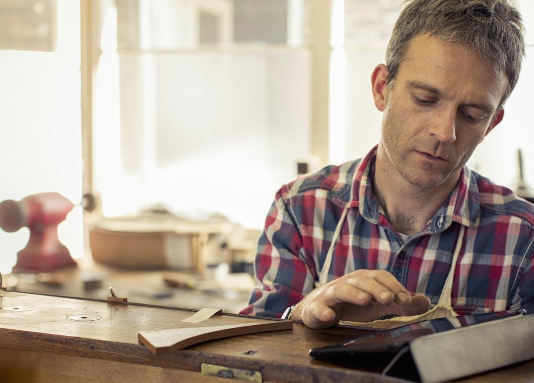 Un homme dans un atelier qui utilise Office365 Business sur une tablette.