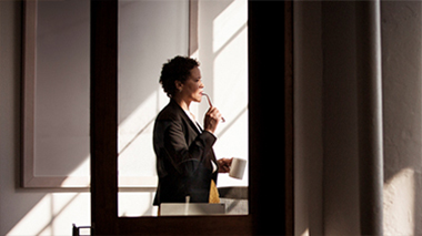 Femme se tenant à une fenêtre. Lisez les questions fréquemment posées sur Visio