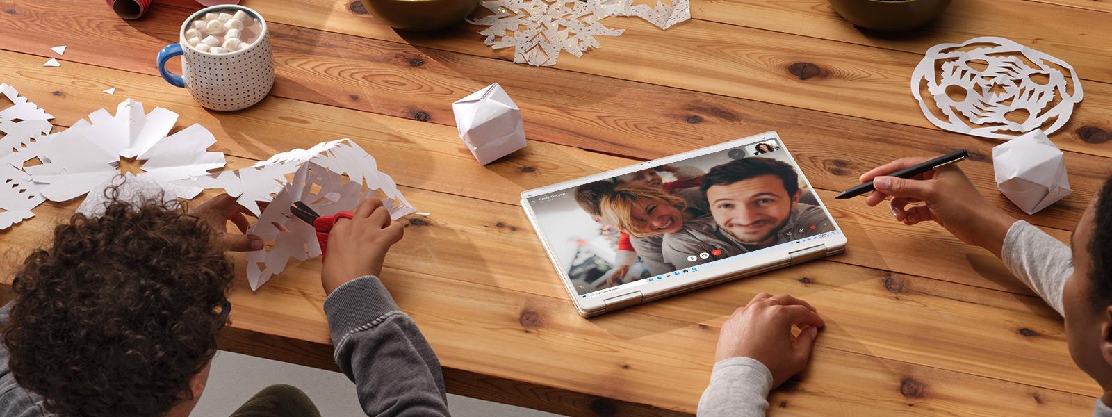 Un PC posé sur une table montrant un appel Skype tandis que deux personnes sont assises à la table en train de faire des flocons de neige