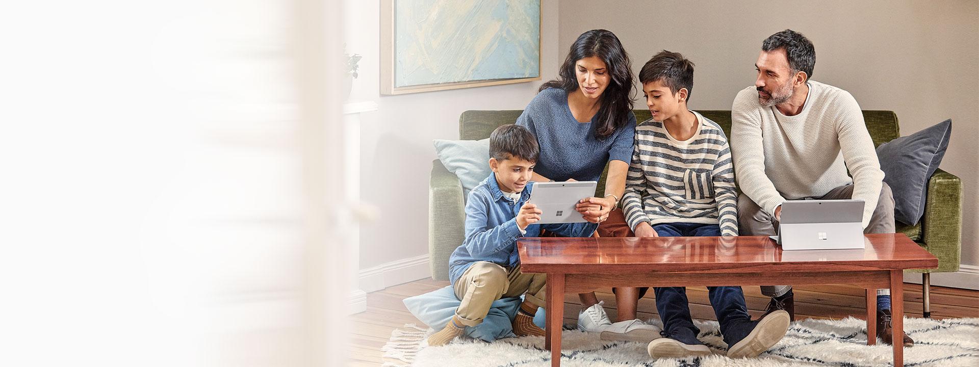 Un homme, une femme et deux garçons qui utilisent deux ordinateurs Microsoft Surface assis sur un canapé à la maison