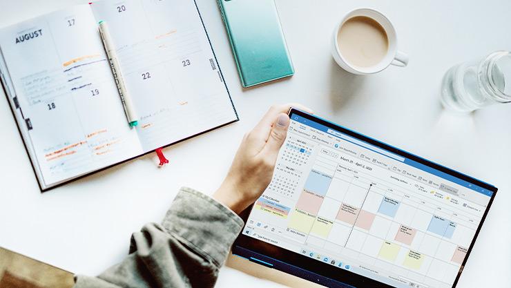 La main gauche d'une personne tient une tablette Windows10 affichant le Calendrier Outlook à côté d'un agenda papier sur un bureau avec un bloc-notes en spirale, du café et de l'eau.