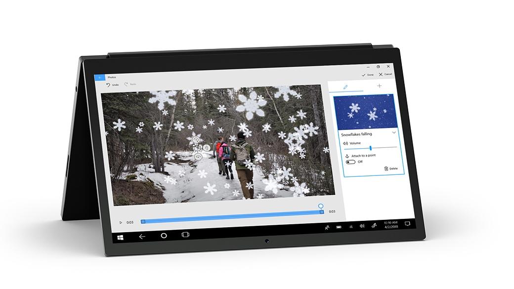 Ordinateur 2-en-1 placé comme un chevalet montrant l'application Photos avec une image de randonneurs dans la forêt avec un effet de flocon 3D superposé