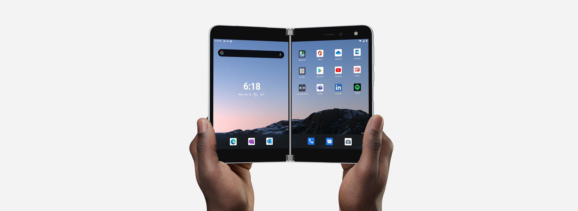 Le double écran du SurfaceDuo est tenu ouvert à deux mains