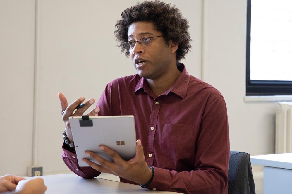 Un travailleur social tient une SurfacePro (5th Gen) with 4G+ en mode tablette dans une main, et le stylet Surface dans l'autre