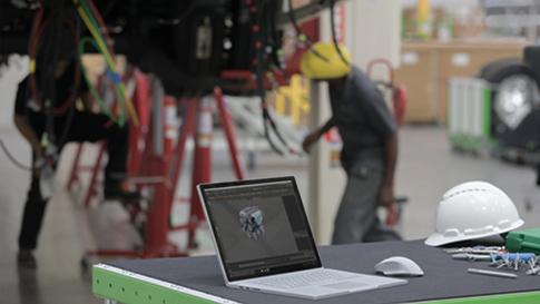 Surface Book 2 avec le logiciel AutoCAD affiché à l'écran dans un atelier de réparation.