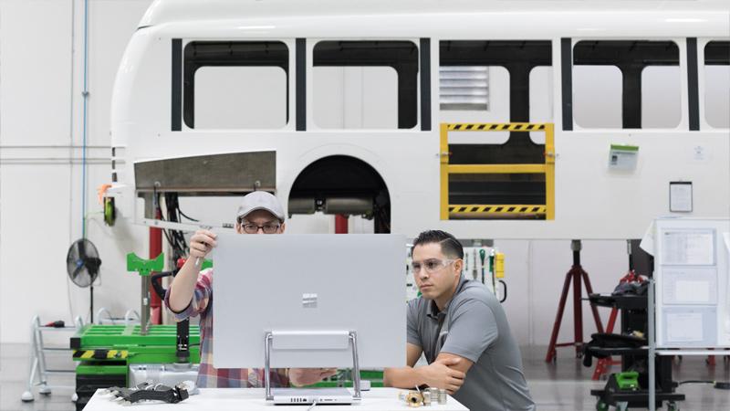 Deux personnes regardant l'écran d'un SurfaceStudio dans un laboratoire de fabrication.