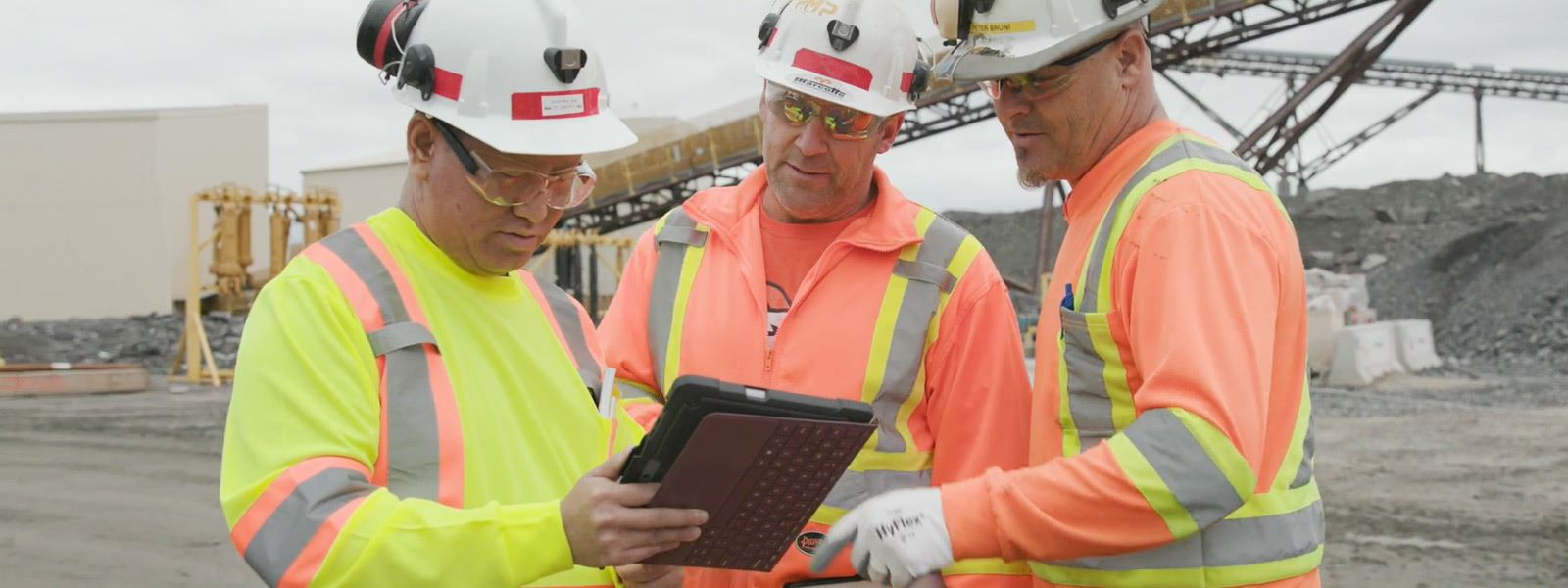 Trois employés de construction regardant une Surface Go sur un site professionnel