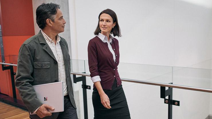 Homme tenant un SurfaceBook dans la main droite et marchant aux côtés d'une femme au travail.