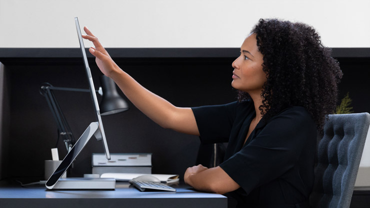 Une femme touche des interfaces grâce à son écran SurfaceStudio2