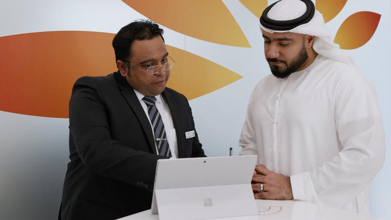 Un employé Mashreq et son client partagent des informations sur une SurfacePro
