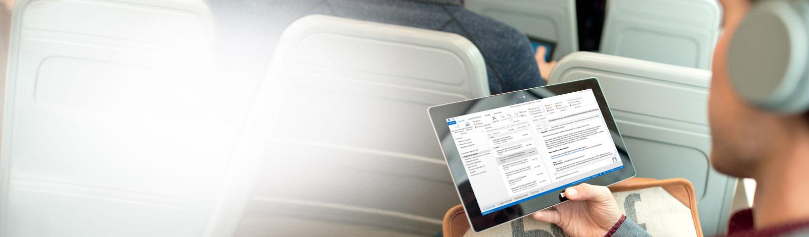 Homme utilisant une tablette, laquelle affiche sa boîte de réception. Accédez à votre messagerie en tout lieu grâce à Office365.