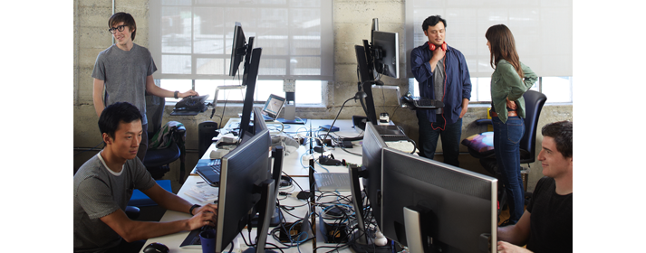 Cinq personnes dans un environnement de travail partagé utilisant un PC ou en train de discuter.