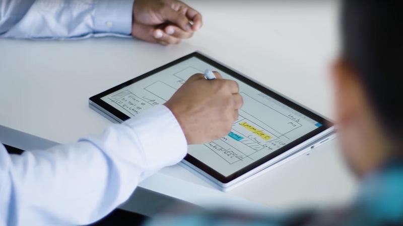 Homme utilisant le stylet sur un Surface Book en mode bloc-notes.