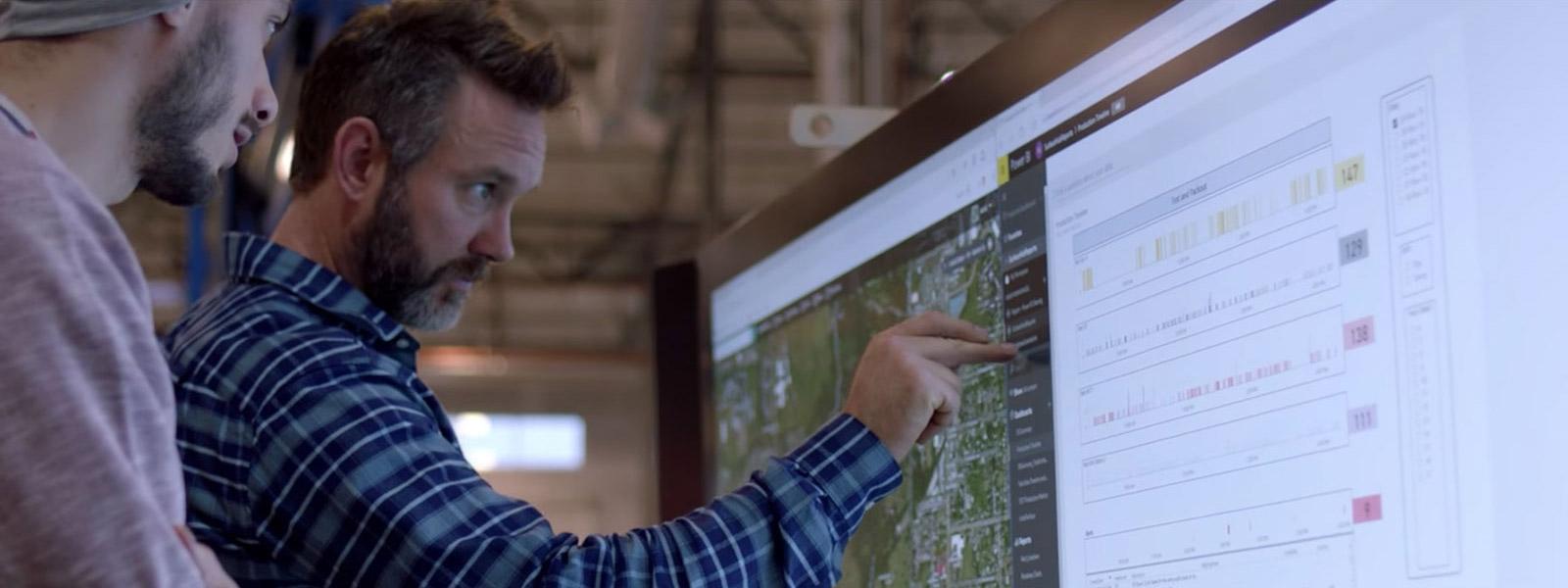 Deux hommes utilisant l'écran tactile sur un appareil Surface Hub