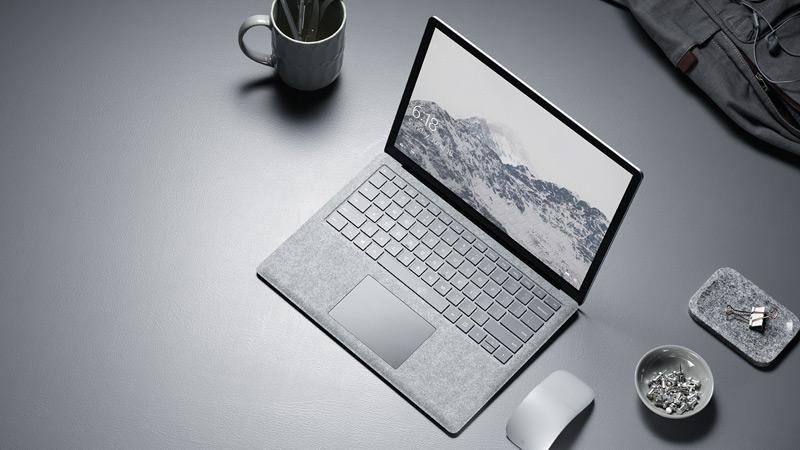 Vue aérienne du Surface Laptop platine avec souris Arc Touch Mouse platine, sur un bureau dans un environnement professionnel