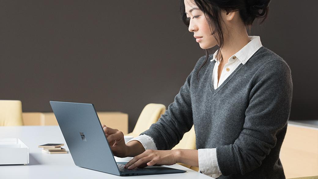 Femme qui tape du texte sur un Surface Laptop bleu cobalt, assise à une table.