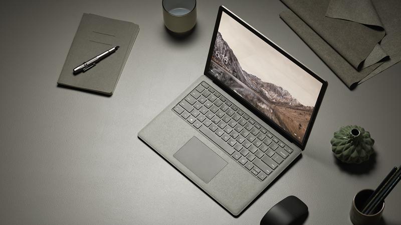 Vue aérienne du Surface Laptop doré avec souris Arc Touch Mouse noire, sur un bureau dans un environnement professionnel.