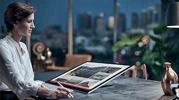 Femme regardant son Surface Studio en mode Studio sur un bureau dans le cadre d'un bureau en hauteur avec une ville visible par la fenêtre en arrière-plan