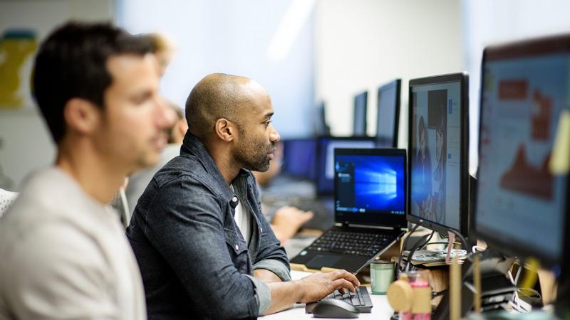 Des hommes qui travaillent sur une rangée d'ordinateurs