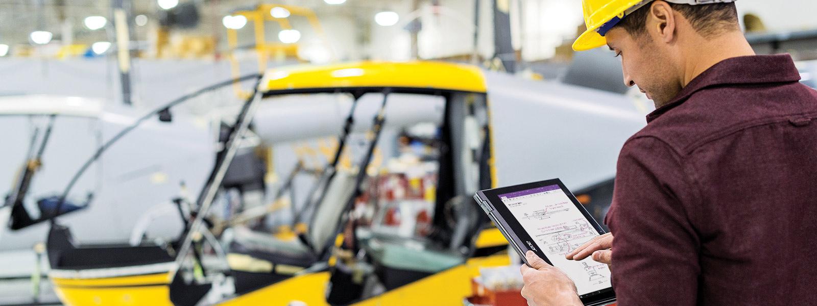 Homme qui consulte une tablette dans une usine