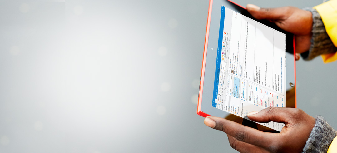 Homme tenant une tablette dans ses mains. Grâce à Office365, vous pouvez travailler en tout lieu.