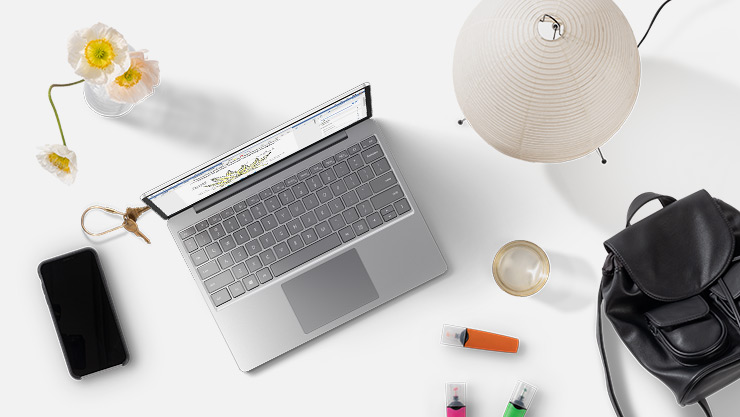 מחשב נישא עם Windows10 מונח על שולחן ליד טלפון, תיק יד, פרחים, טושים, משקה ומנורה.