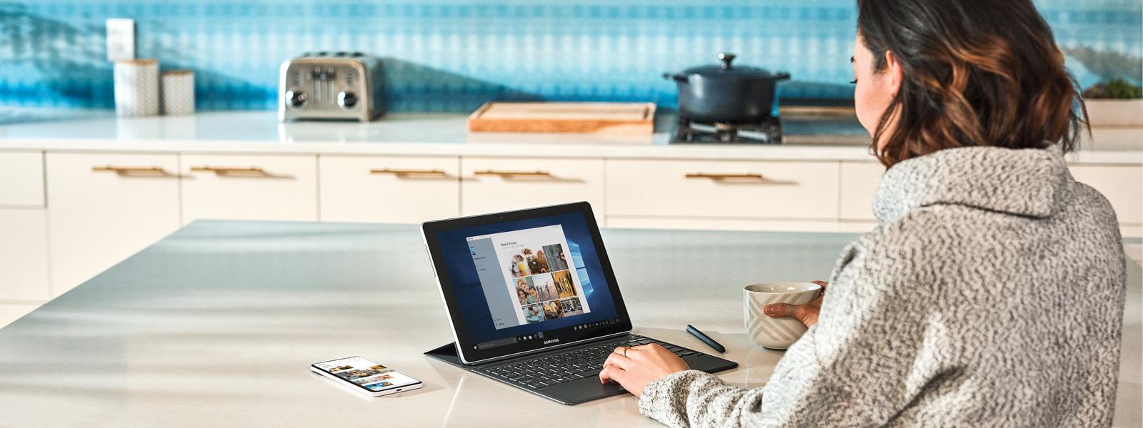 אישה יושבת לצד דלפק במטבח ומשתמשת ב-Windows 10 על מחשב נייד, עם הטלפון הנייד שלה