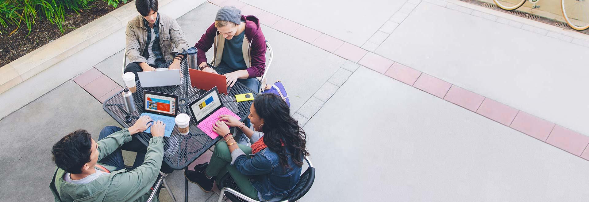 ארבעה תלמידים היושבים ליד שולחן בחוץ ומשתמשים ב- Office 365 למגזר החינוך במחשבי Tablet.