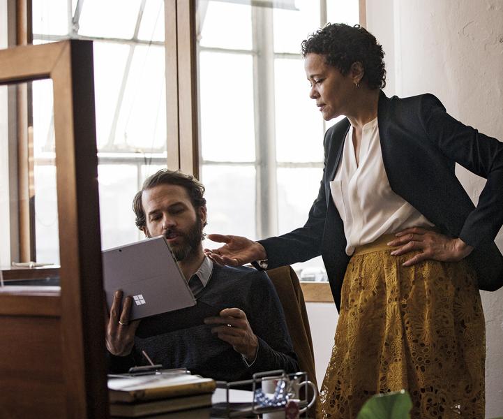 שני אנשים במשרד מביטים במחשב נישא עם Windows