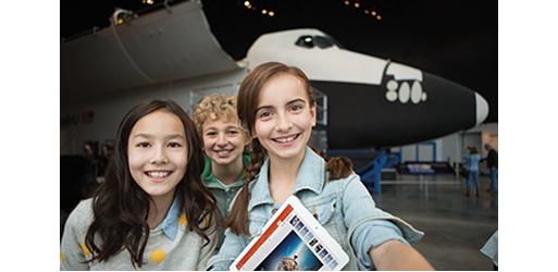 שלושה ילדים מחייכים לפני מטוס, קבל מידע על שיתוף פעולה עם אחרים ב- Office