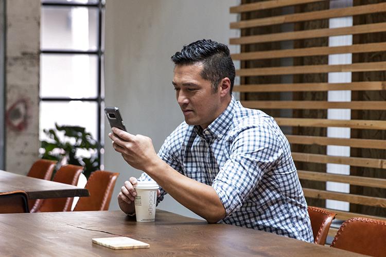 אדם יושב בחדר ישיבות ומביט במכשיר נייד