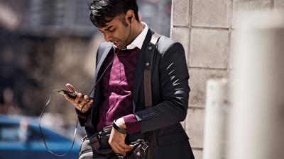 אדם עומד בחוץ, משוחח במכשיר נייד ומרכיב אוזניות