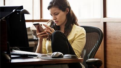 אישה יושבת ליד שולחן ומביטה במכשיר נייד