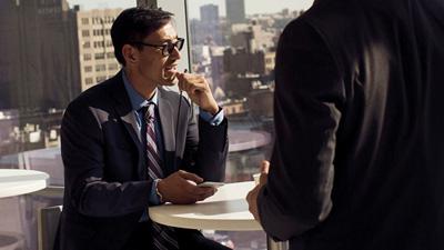 אדם יושב ליד שולחן עגול במשרד ומשתמש במכשיר נייד